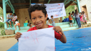 Almer, a 6 year old boy, shows his drawing during a psychosocial activity conducted by World Vision in Kidapawan City
