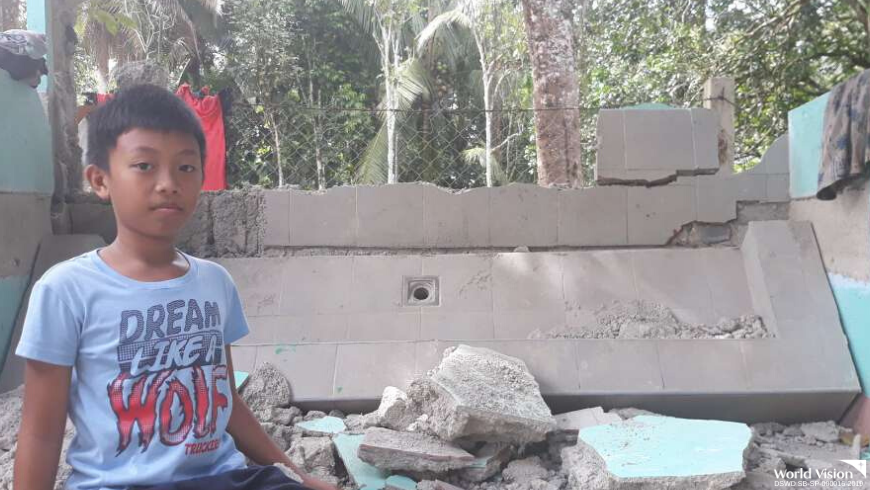 "Rjay, 11 years old, checks the debris of his school's newly constructed handwashing facility. He and his family are seeking temporary shelter in a school in Kidapawan City. ""I hope God will touch the hearts of the people and help us in our situation,"" he shared."