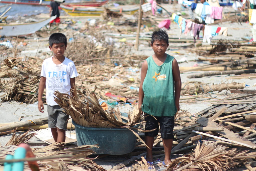 After typhoon Kamurri destroyed their house, Mark Glenn, 11 and his younger brother John Quiel spend their days helping their father build a makeshift shelter.